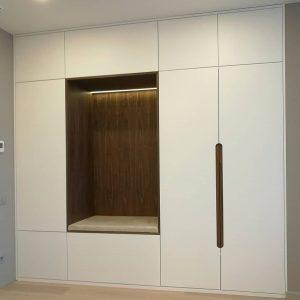 Встроенный белый шкаф с интегрированными деревянными ручками